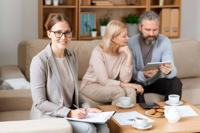 INSURANCE CONSULTANT SITTING WITH FAMILY IN LIVING ROOM GOING OVER DETAILS